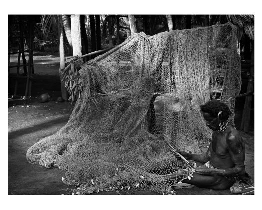 Man working on fish net, Komabun village, Collingwood Bay, PNG