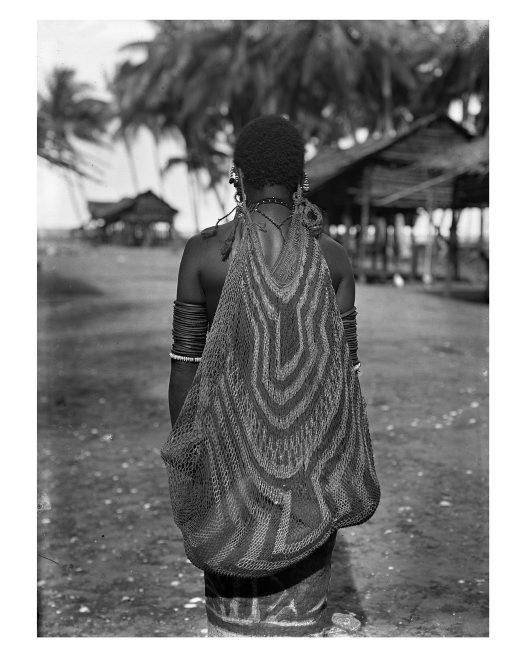 Woman carrying baby in string bag, Ambasi village, Oro Province, PNG