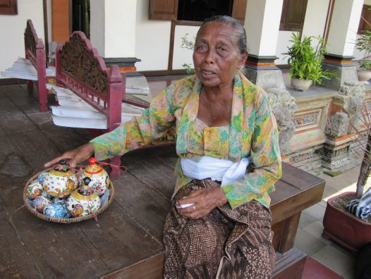Ibu Agung offers painted wooden eggs and coconut shells for sale