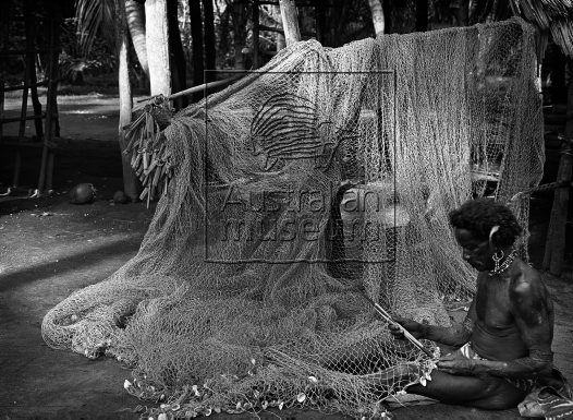 Man working on a fish net Komabun village, Collingwood Bay Oro Province May 1921