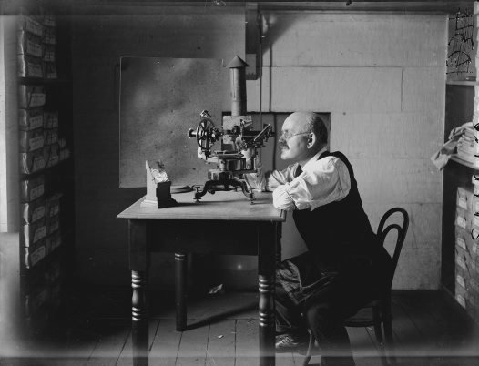 Charles Anderson measuring the facets of crystals with the museum's goniometer. 1919