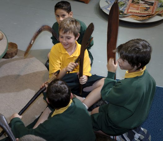 Students with Aboriginal men's artefacts
