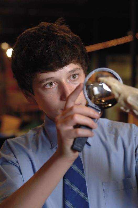 Secondary student with magnifying glass