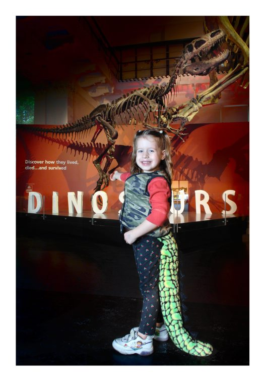 A pre-schooler dressed up as a dinosaur