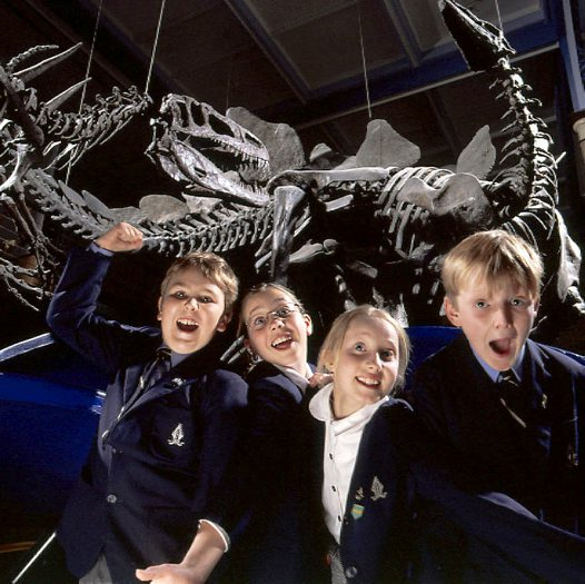 Four students with dinosaur skeletons