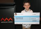 Six-year-old Julian Perros presents his cheque to Lizard Island Reef Research Foundation