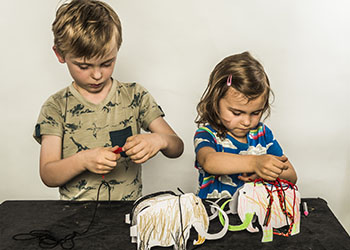 Two children crafting cardboard mammoths and decorating them using crayons and nylon strings on a table top
