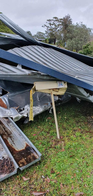 """Our letterbox smashed with our flying roof behind it: Beauty Point windstorm/mini tornado, 27th July 2020. People here in Beauty Point have yellow ribbons with climate action on them on their letterboxes.  After the fires it was the Bega Valley Climate Mobilisation Facebook group that suggested yellow ribbons. So I went off and bought up ribbon, cut it up into strips and while watching tv I just wrote """"climate action"""" with a sharpie pen on each ribbon and gave them to neighbours, for themselves and others. Now if you drive around Beauty Point you'll see heaps of yellow ribbons from letterboxes and gates. We were all evacuated three times during January..."""