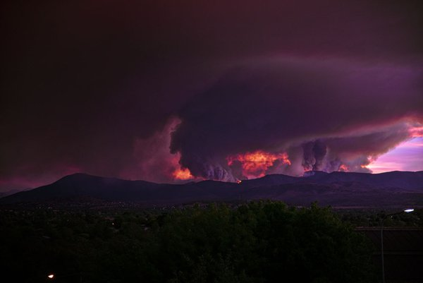 Fires out of control are spreading quickly in the Brindabella mountains. At night, the flames illuminate this huge dark cloud. The fires threaten suburbs in South Canberra. A massive cloud of smoke spreads over the city.