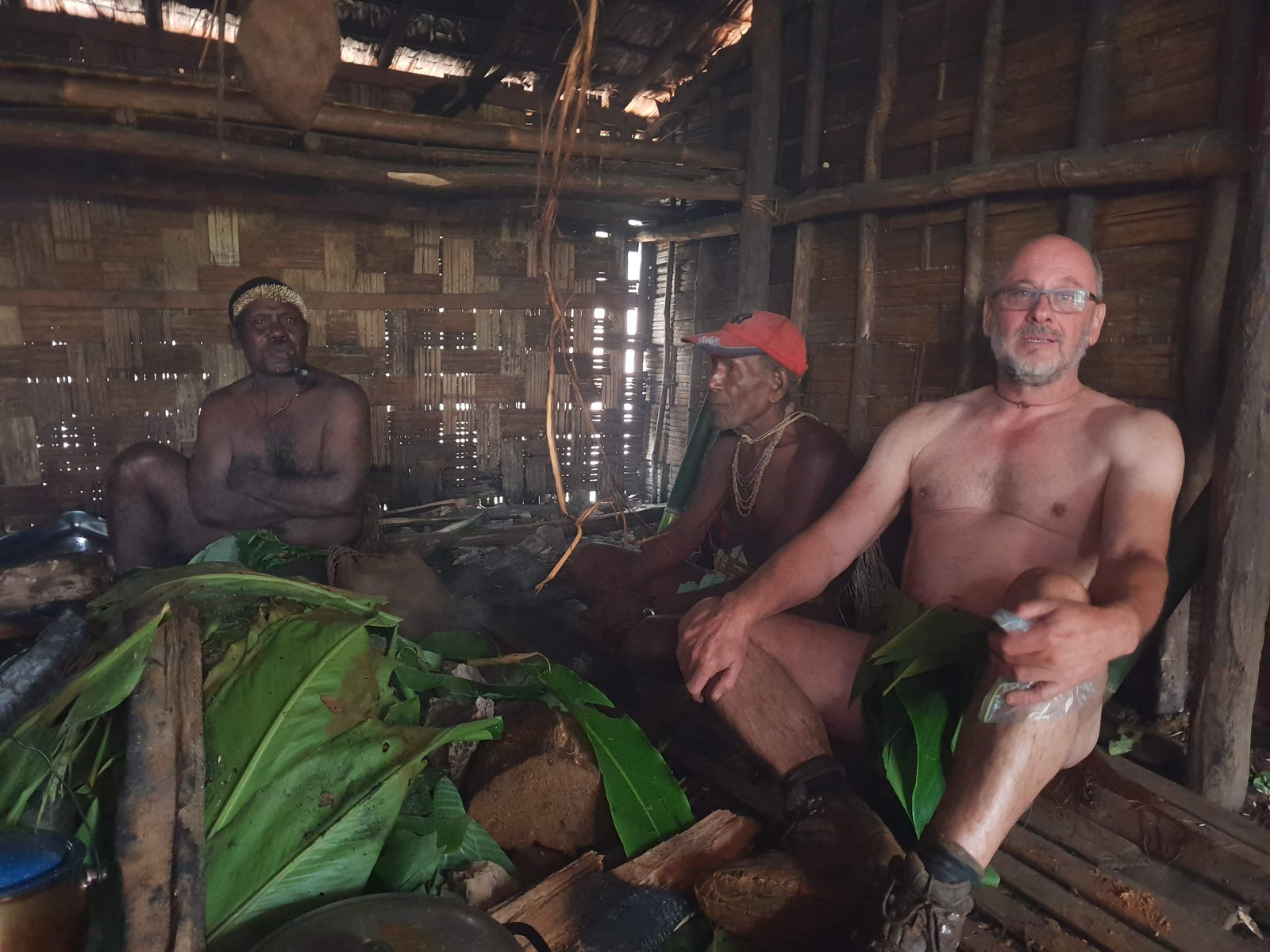 Tim Flannery rests in a hut, wearing the traditional attire of a banana leaf