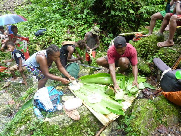 Kwaio community preparing a meal with banana leaves, Malaita.