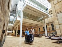 Man who uses a wheelchair and friend in Hintze Hall