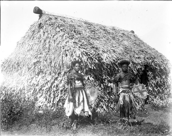 Two people in front of a hut, Davuilevu Mission, Fiji