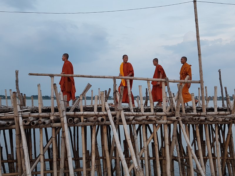 Monks on bamboo bridge
