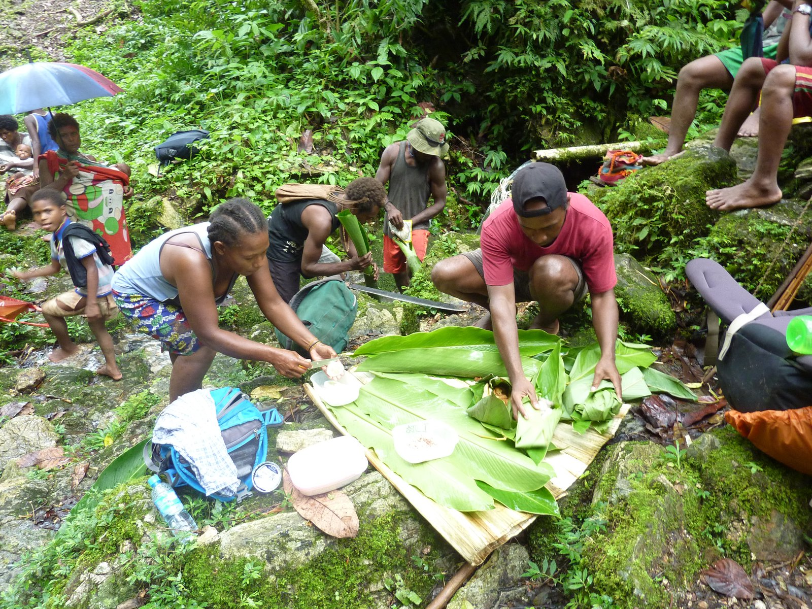 Kwaio community preparing a meal with banana leaves, Malaita.