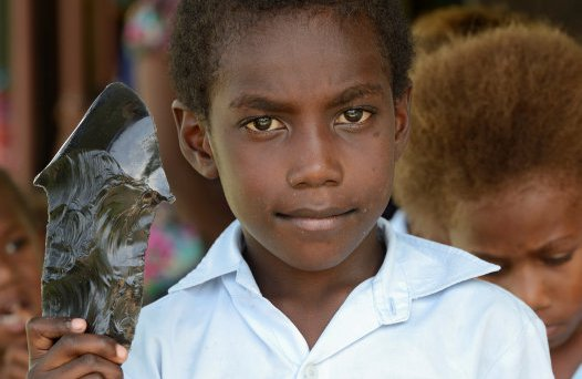 Student with replica obsidian tool in Papua New Guinea