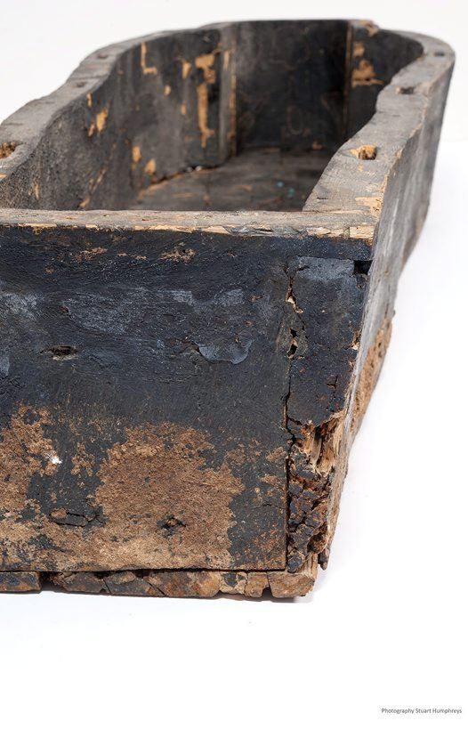 Coffin trunk, showing some damage and mud at the bottom part.
