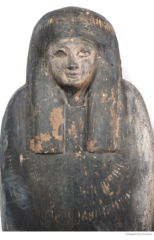 Carved head with traces of dirt and mud.