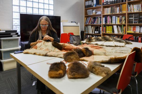 Vicki Couzins working on a possum cloak.